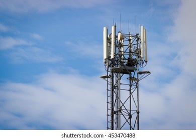 Technology on the top of the telecommunication GSM (4G) tower (antenna, transmitter), blue sky, white clouds.