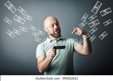 Technology, online banking, money transfer, e-commerce concept. Happy bearded middle-aged man using smartphone dollar bills flying on grey wall background. Internet earnings concept