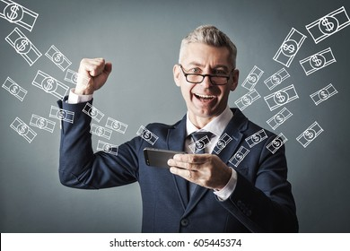 Technology, online banking, money transfer, e-commerce concept. Businessman using smartphone dollar bills flying on grey wall background. Internet earnings concept