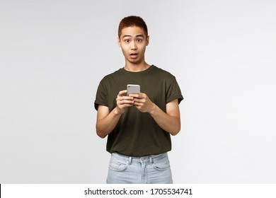 Technology, online lifestyle and communication concept. Portrait of surprised and confused asian guy asking question as receive strange message, holding mobile phone and look indecisive