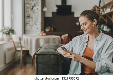 Technology in our life. Waist up portrait of young happy woman on sofa watching video on mobile phone with wireless earbuds