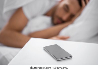 technology and people concept - close up of smartphone on bedside table near young man sleeping in bed at home in morning