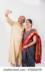 Technology and people concept - indian senior couple taking selfie with mobile camera, isolated over white background