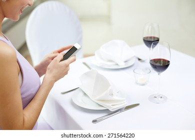 technology, people, food and dinner concept - close up of woman with smartphone at restaurant