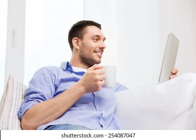 technology, people and leisure concept - handsome man with tablet pc computer and cup drinking coffee or tea at home