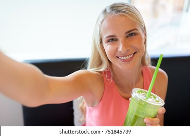 technology, people and leisure concept - happy woman with smoothie drink or vegetarian shake taking selfie at restaurant