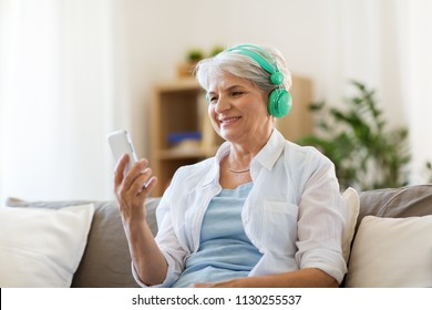 technology, people and lifestyle concept - happy senior woman in headphones and smartphone listening to music at home