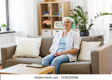 technology, people and lifestyle concept - happy senior woman in headphones and tablet pc computer listening to music at home
