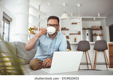 Technology, people and lifestyle concept - happy man with laptop computer drinking coffee or tea at home. Joyful bearded man working indoors at his living room