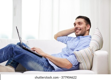 technology, people and lifestyle concept - smiling man lying on couch with laptop computer at home