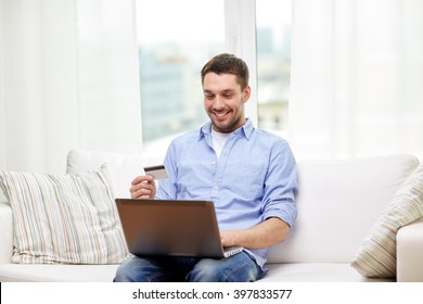technology, people and online shopping concept - smiling man with laptop and credit card at home
