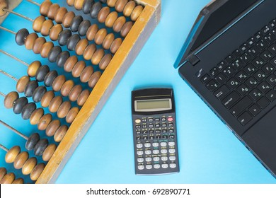 Technology progress concept, vintage abacus, calculator and new laptop on the blue background.