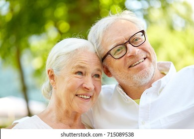 technology, retirement and old people concept - happy senior couple taking selfie and hugging at summer park
