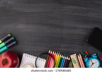 Technology and school concept. Top above overhead view photo of smartphone apple and colorful stationery isolated on blackboard with copyspace - Shutterstock ID 1749085685