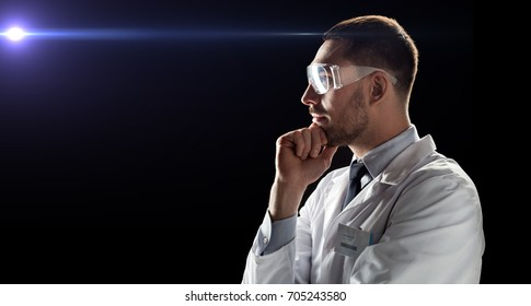 technology, science, and people concept - male doctor or scientist in white coat and safety glasses over black background with laser ray