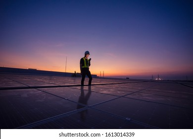Technology solar cell, Engineer service check installation solar cell on the roof of factory on the morning. Silhouette technician with solar cell on the roof of factory under morning sky.