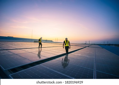 Technology solar cell, Engineer service check installation solar cell on the roof of factory on the morning. Silhouette technician inspection and repair solar cell on the roof of factory.