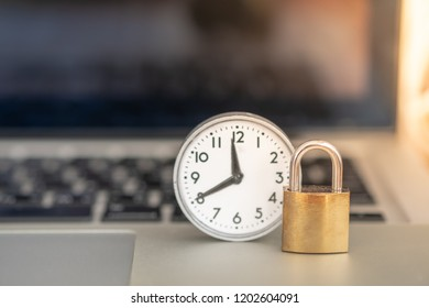 Technology , Time and Security Concept. Close up of master key lock with vintage round clock on laptop computer notebook.