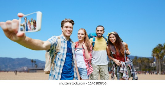 technology, travel, tourism, hike and people concept - group of smiling friends with backpacks taking selfie by smartphone over venice beach background in california