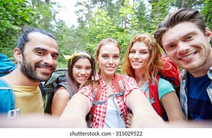 technology, travel, tourism, hike and people concept - group of smiling friends walking with backpacks taking selfie by smartphone or camera in woods