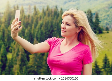 With technology, traveling is easier. Beautiful young modern girl traveler with travel bag smiling and taking pictures or doing selfie on a background of mountains or nature