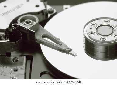 Technology - very old Hard Disk, data backup medium, detail with shallow depth of field, in color, HDD.  The platters with magnetic heads arranged on a moving actuator arm.