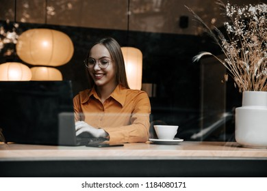 Technology. Work. Freelance. Girl is working with her laptop and smiling while sitting in cafe