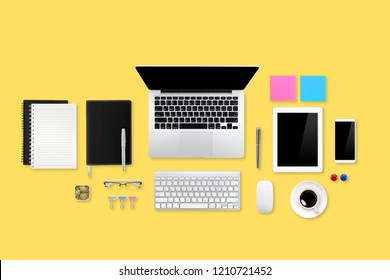 technology working desk with laptop computer, office supplies, coffee cup, tablet and cell phone on yellow pastel background