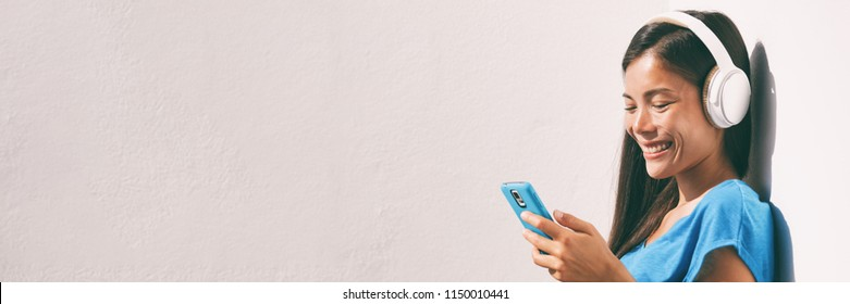 Technology young people - Asian woman listening to music with headphones and smartphone online with wifi - Home lifestyle banner panorama.
