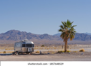 TECOPA, CA/USA - NOVEMBER 19, 2020: Airstream Travel Trailer and palm tree shown against a desert landscape in Inyo County.