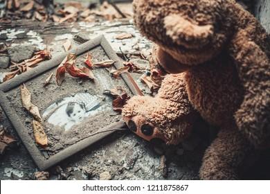 Teddy bear in an abandoned building. Destruction after the fighting. Old photo in frame. Lutsk. Ukraine. October 19, 2018.
