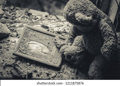 Teddy bear in an abandoned building. Destruction after the fighting. Old photo in frame. Lutsk. Ukraine. October 19, 2018.
