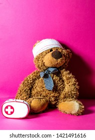 Teddy bear with bandage at the head and first aid kit for mishap concept of healthcare education over pink background