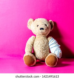 Teddy bear with bandage to heal a broken or injured arm at the doctor's, pediatrician's or at the hospital, pink background