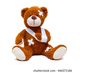 Teddy bear with bandages and broken hand isolated on white background