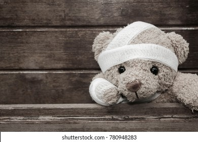 Teddy bear with bandages and broken hand on wood background in blackvand white,copy space,