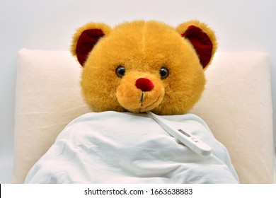 Teddy bear in bed, sick and feverish, with the thermometer in his mouth