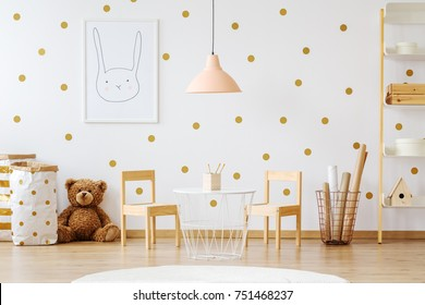 Teddy bear between paper bags and wooden chairs in child's room with pastel lamp above table