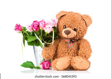 Teddy bear and bright flowers in the vase on white background