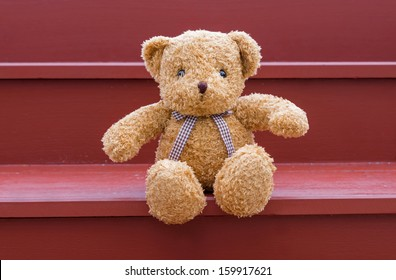 TEDDY BEAR brown color sitting on red staircase