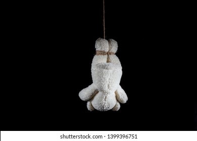 teddy bear doll hanging with hemp rope on black background
