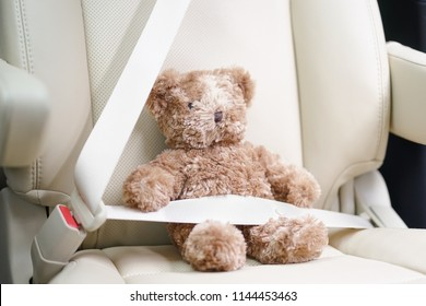 Teddy bear, fasten the seat belt for your child safety. Child in car concept. Soft focus on the teddy bear's nose.