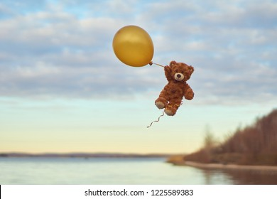 Teddy bear flying to the sky with a big yellow ball.  A bear fly over the lake. Winnie Pooh flying with balloon.  Pooh balloon travel. Aerial travel. Happy toys flies.UFO. Winnie the Pooh.