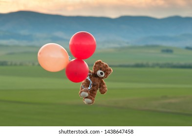 Teddy bear flying to the sky with a big yellow and red balloons.  A bear fly over the fields.  Pooh balloon travel. Aerial travel.