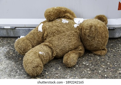 Teddy bear in garbage with snow, old toys, childhood abandonment