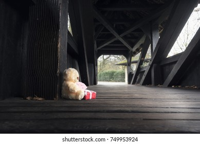 Teddy bear with gift and message - Gifting theme image with a stuffed bear toy holding a red gift box and a miss you note, sitting alone on an empty wooden bridge.