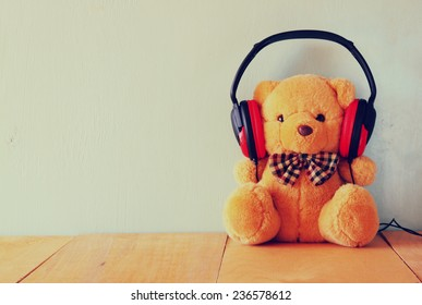 teddy bear with headphones over wooden table