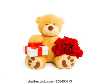 Teddy bear holding gift box and bouquet of red roses, valentines day. Studio shot, over white background with copy space.