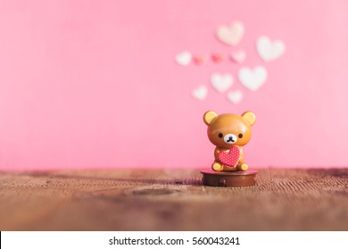 Teddy bear holding a heart on the old wood floor with pink background blur.