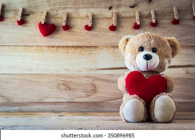 Teddy bear holding a heart-shaped pillow with plank wood board background